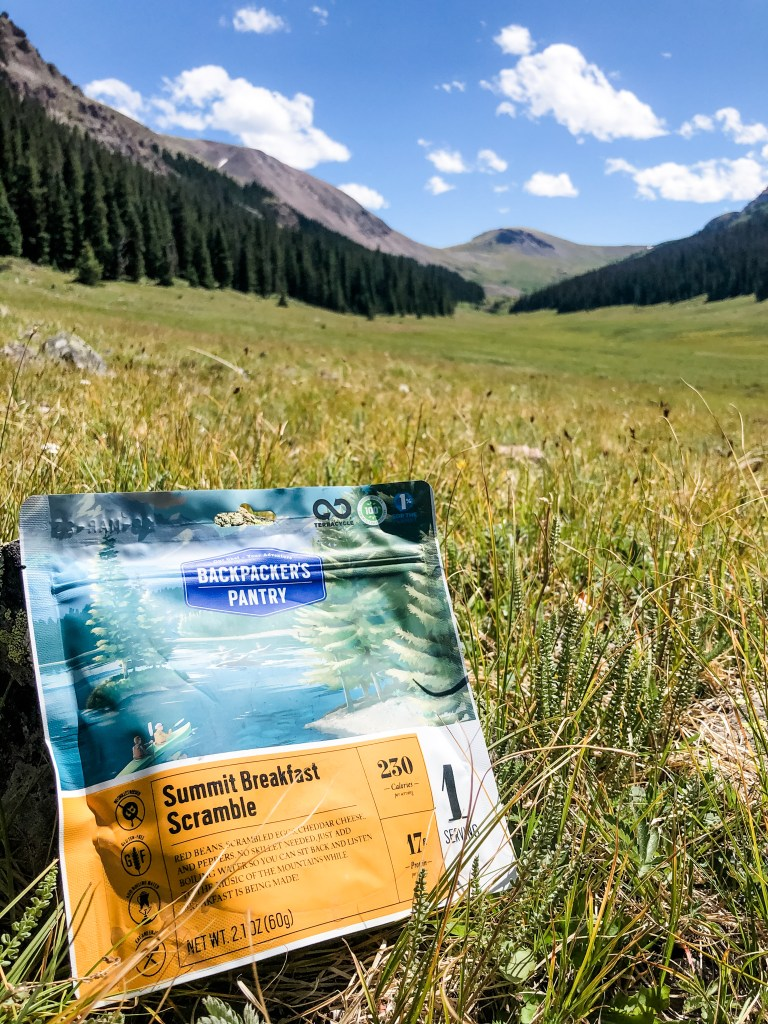 Backpacker's pantry freeze dried meal sitting in the grass with mountains in the background