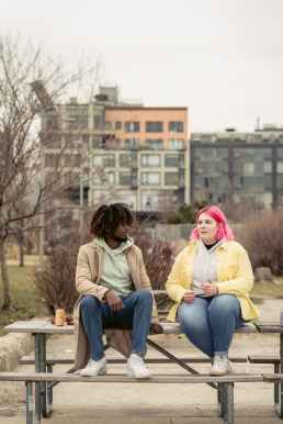 A Black person and white person sit talking on a table at a park. They seem to be discussing a boundary and how to address it in their relationship. If you would like support on how to set boundaries, please reach out. I am an HSP therapist in Berkeley, and would be happy to help.