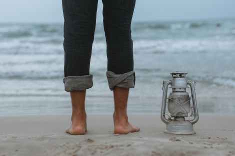 A person standing on shoreline beside gray tubular lantern. They are using the feel of the sand on their feet to ground themselves. If you are an empath, HSP, or intuitive who would like to learn how to ground, reach out. I am a somatic ecotherapist in Berkeley, CA.