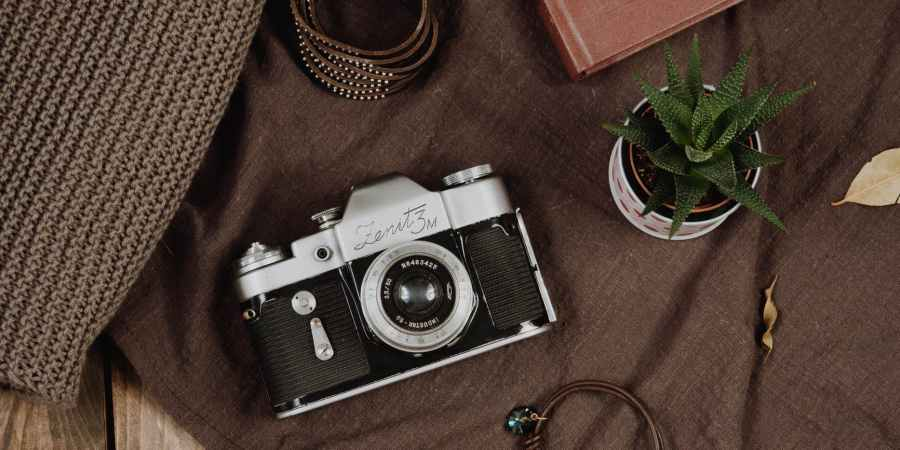 analog camera and bracelets on brown textile