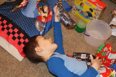 Christmas morning opening presents. Throw-up bucket next to him.