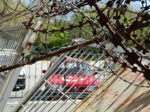 See the white star and crescent featured on the Turkish flag painted on the hood of the car....behind the fence and barbed wire.