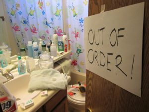 crowded bathroom with out of order sign on the door