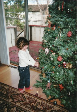 little girl in white top and jeans putting ornaments on a Christmas tree