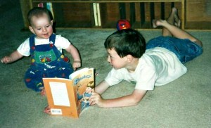 five year old boy reading a book about snakes to his delighted little sister