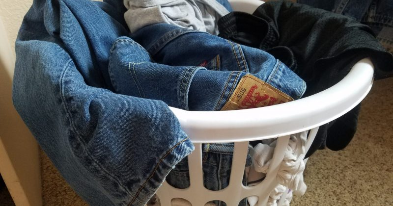 jeans crammed on top of an overflowing laundry basket