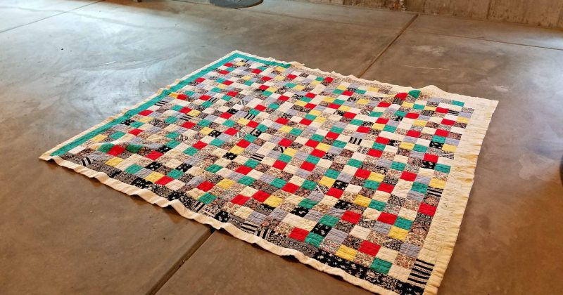 homemade quilt in red, yellow, green, black and white colors on a concrete basement