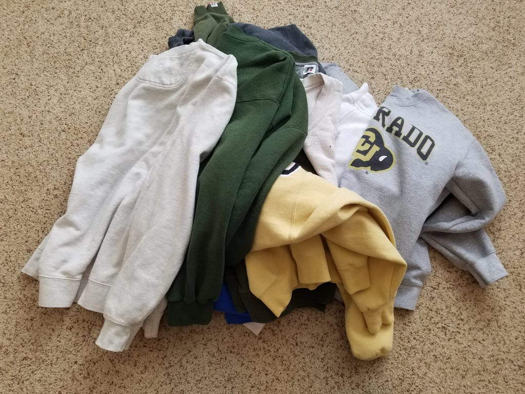 pile of sweatshirts white, bottle green, yellow and gray colors on a beige carpet
