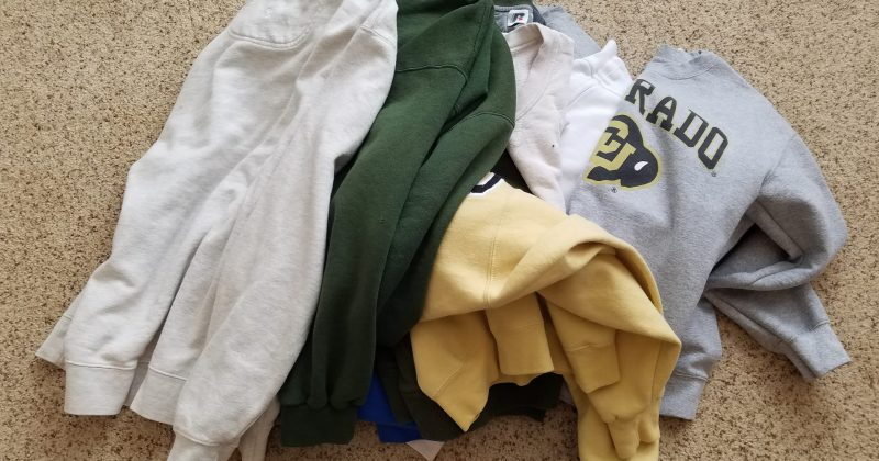 pile of sweatshirts (white, bottle green, yellow and gray colors) on a beige carpet
