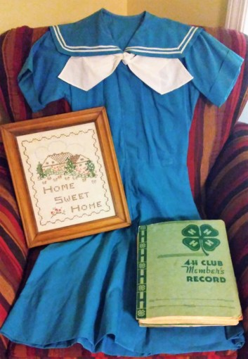 My 4-H uniform and record book. I cross-stitched this Home Sweet Home when I was 14. I earned a red ribbon for refinishing the frame.