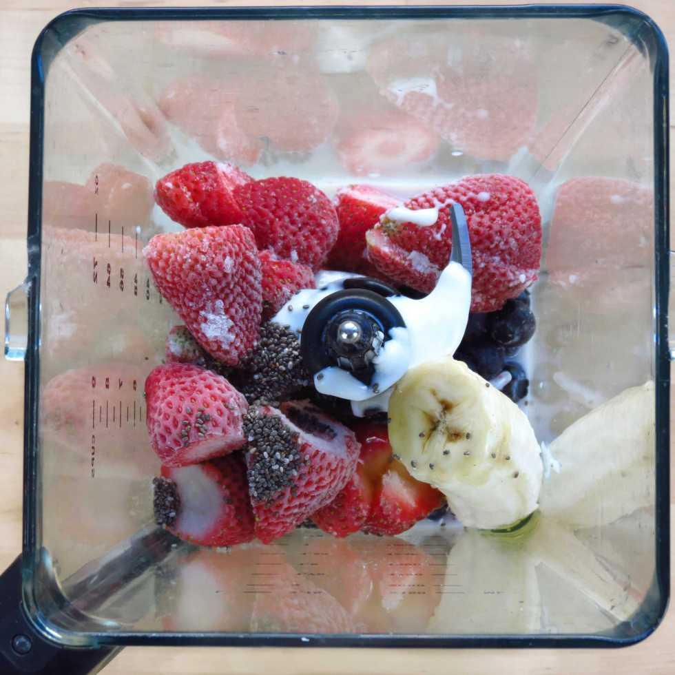 Blending strawberries, blueberries, banana, yogurt, milk, honey and chia seeds for Berry Banana Chia Smoothie