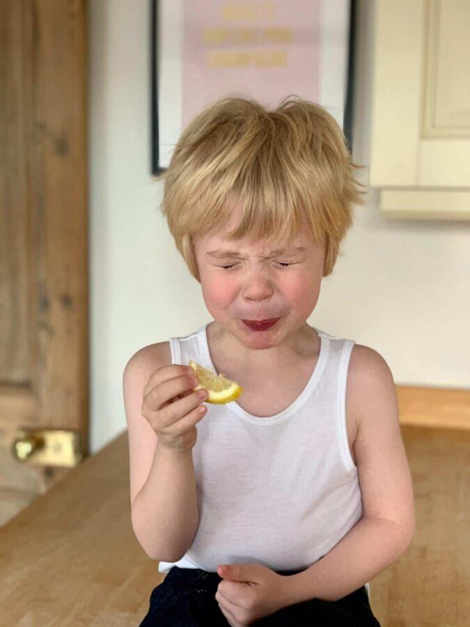 Little boy tastes sour lemon