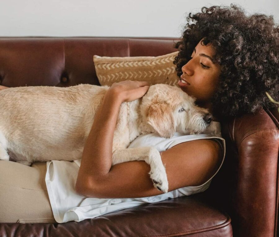 Woman lying on brown leather couch comforting dog