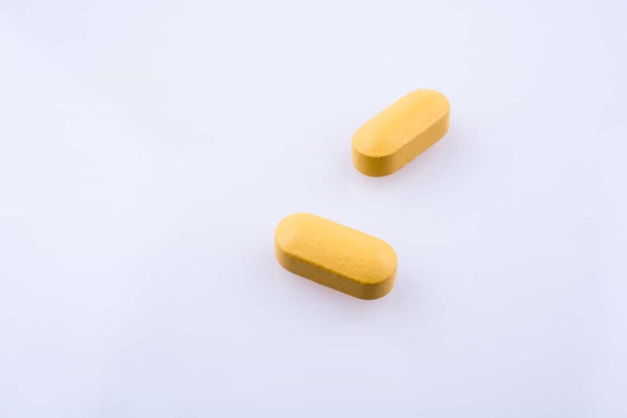 Yellow pills on white background