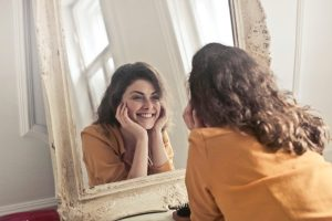 a woman smiling in front of a mirror