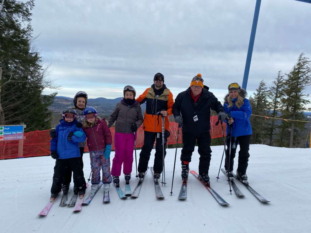 a group skiing and posing on top of the skii lift