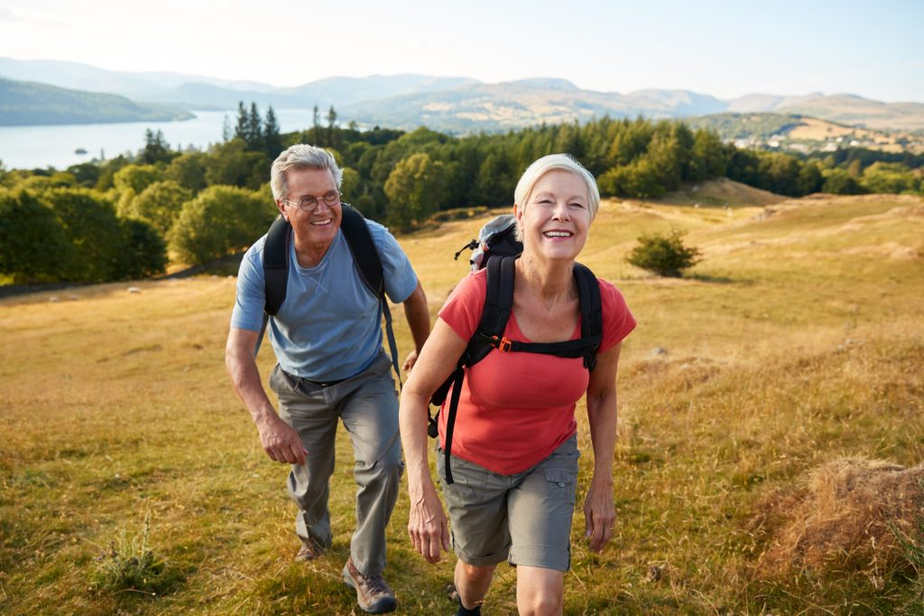 an elderly couple hiking up a field and smiling