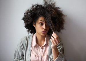 a woman is holding a strand of her curly hair and pursing her lips