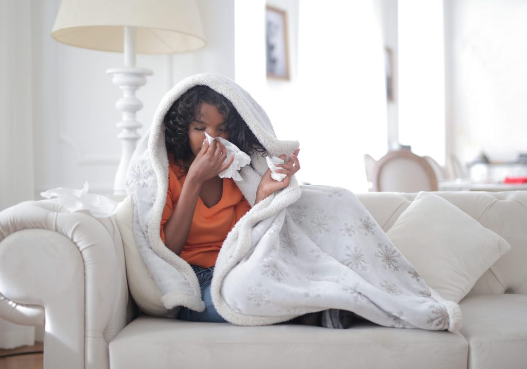 a woman is blowing her nurse and lying on top her couch underneath a blanket.