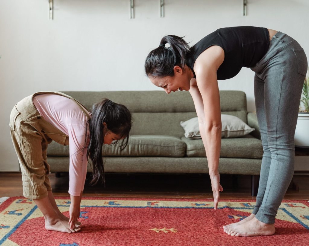 a mother wearing a black top and grey yoga pants and a young daughter wearing a long sleeved pink shirt and brown overalls are trying to touch their feet.