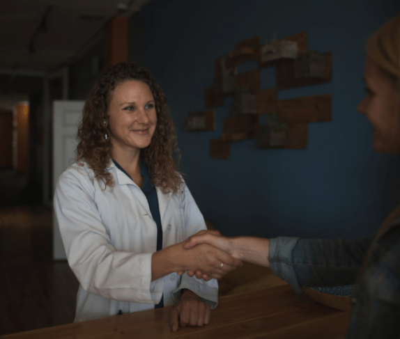 A young woman with dark curly blonde hair and a white lab coat is smiling and shaking hands with an unknown woman.