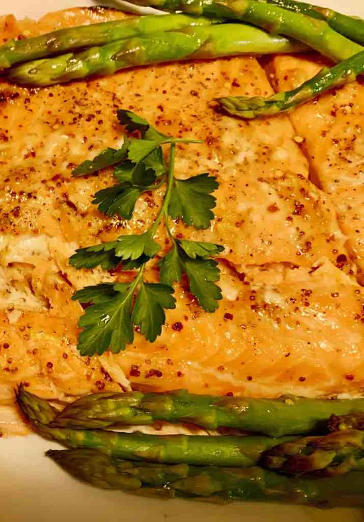 Grilled Salmon on Cedar Plank with cilantro and grilled asparagus on the side on a white dplate