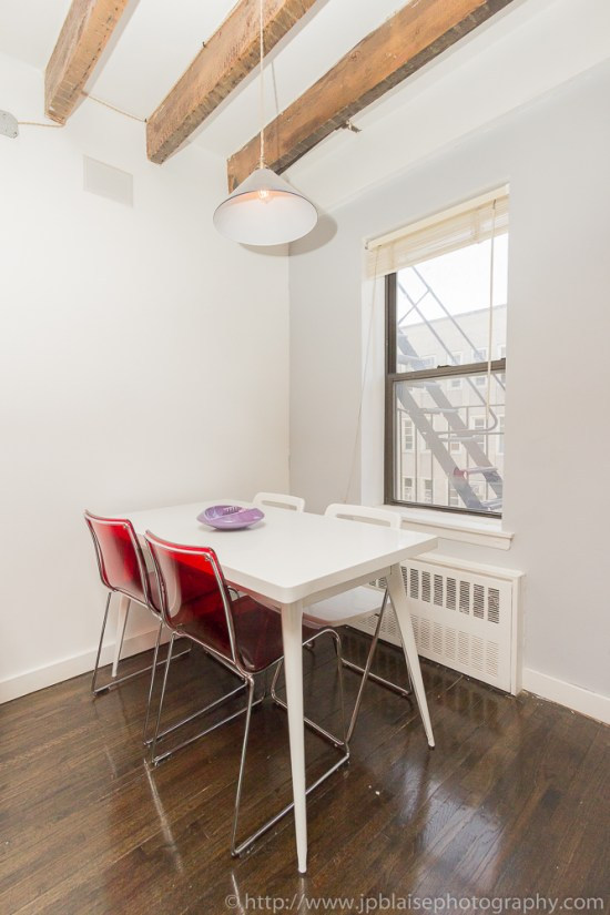 Dining table with modern design in the living room of a one bedroom apartment in New York City