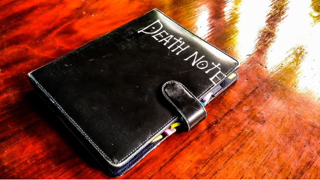 a black note book with the words death note lies on a brown table