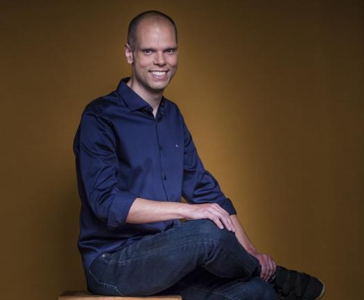 De camisa azul e calça jeans, Bruno Covas, careca devido à quimioterapia, sorri sentado em um caixote