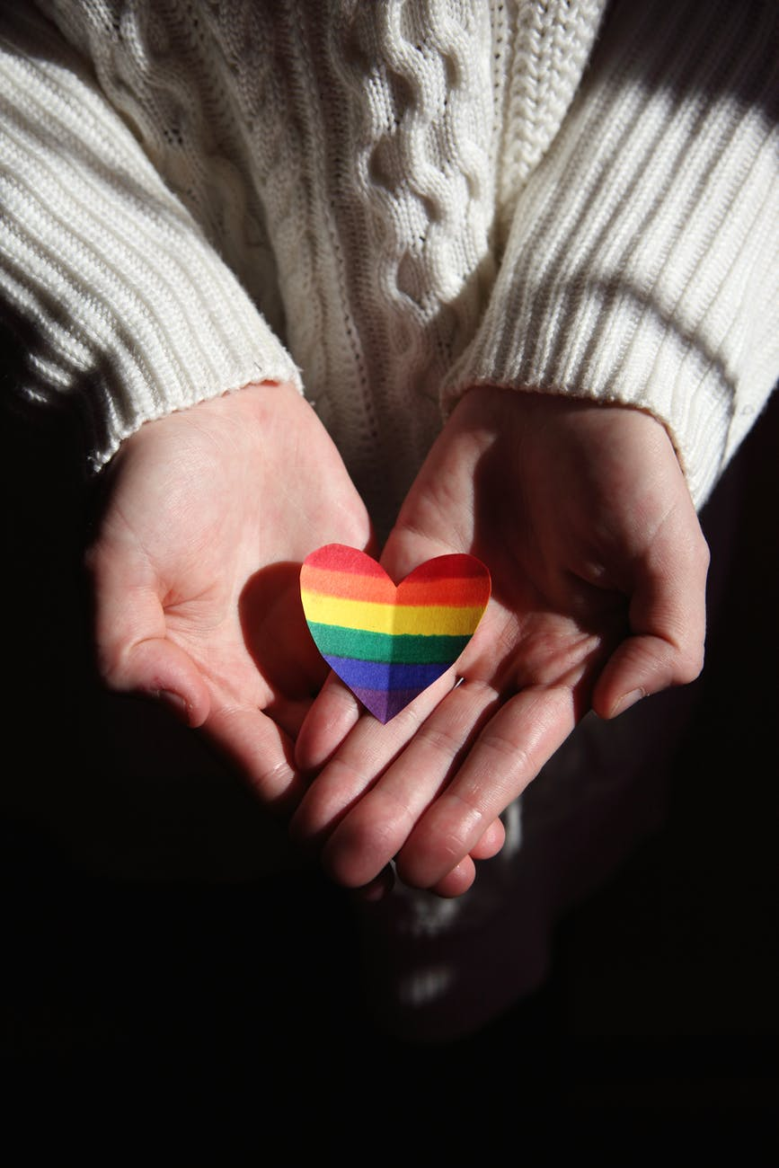 person holding multi colored heart shaped ornament