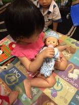 Feeding the baby doll.