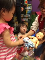 Changing the baby doll.