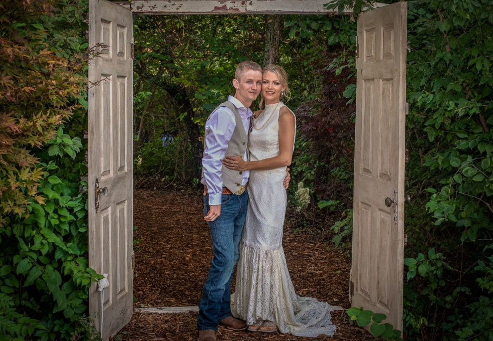 Bride and groom posing in front of the rustic doors at The Red Bud Party Barn Venue in Douglass, KS