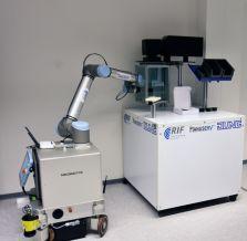 Derselbe Roboter fährt unterschiedliche Arbeitsplätze autonom an. Hier nimmt er das Netzteil der Firma Jung auf und platziert es exak t in der Laserbeschriftungskabine.