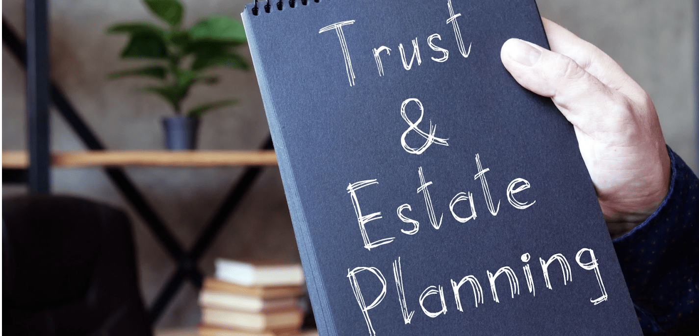 image of a hand holding a notepad with the words trust and estate planning on the front
