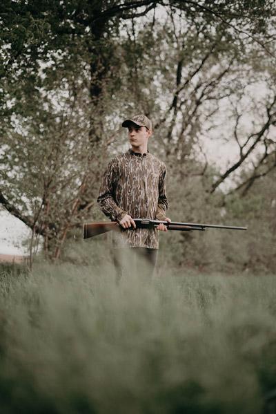 young man outdoors holding shotgun