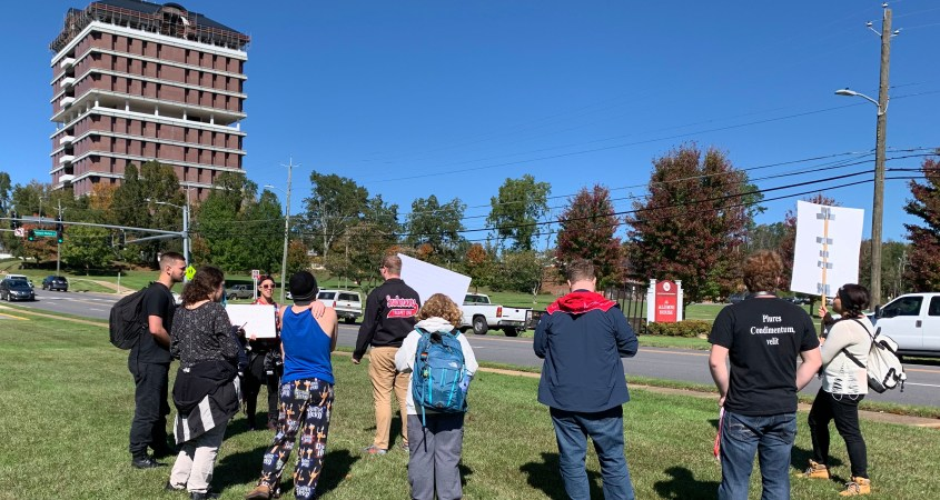 Students protest on the lawn of the Theron Montgomery Building as traffic passes by on Pelham Road. (Scott Young/The Chanticleer)