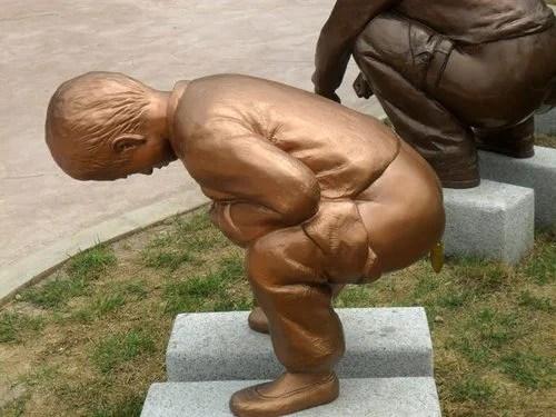 sculpture d'enfant qui fait caca