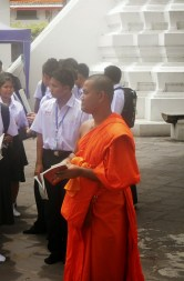 Buddhist monk leading school group through temple complex in Bangkok.