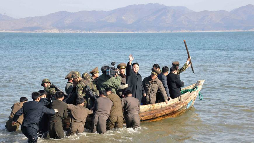 Rallying the troops: North Korean leader Kim Jong Un waves at military officers after inspecting the Wolnae Islet Defense Detachment, near the country's western sea border with South Korea, on March 11.