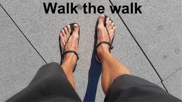Foto de unos pies con sandalias minimalistas y el mensaje: Walk the walk.