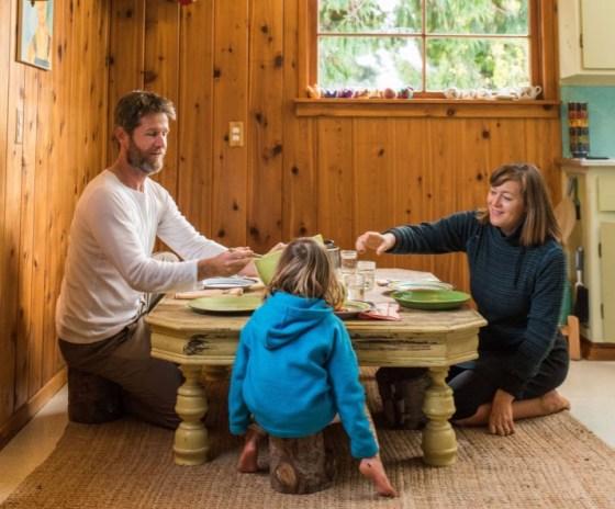 Familia de Katy Bowman a la mesa, sentados en el suelo.