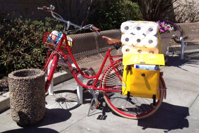 Lady Fleur shows one way to transport cubic yards of toilet paper on a bicycle.