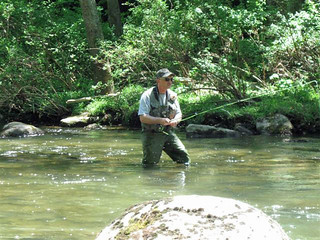 Photo of man Fly fishing while wading in a stream