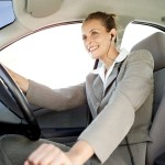 Woman Driving a Car and Wearing Earphones --- Image by © Royalty-Free/Corbis