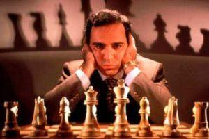 Garri Kasparov mirando de frente con sus manos en la cabeza posando con un tablero de ajedrez