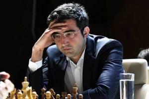 Vladimir kramnik pensando con una mano en la frente y de bajo un tablero de ajedrez