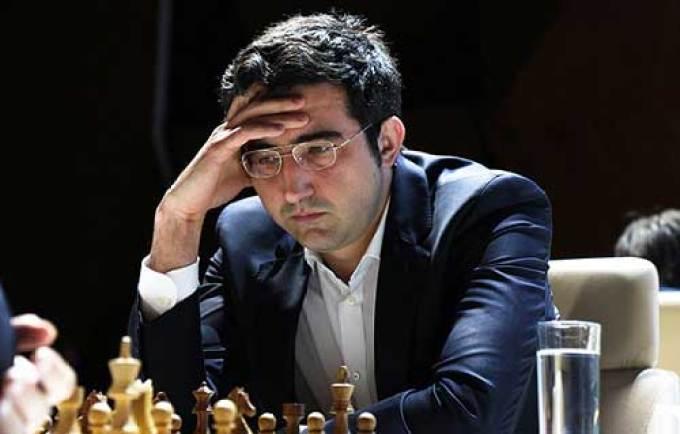 kramnik pensando con una mano en la frente y de bajo un tablero de ajedrez