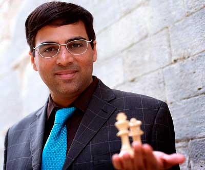 Anand posando en foto de frente sujetando dos piezas de ajedrez en su mano izquierda rey y dama