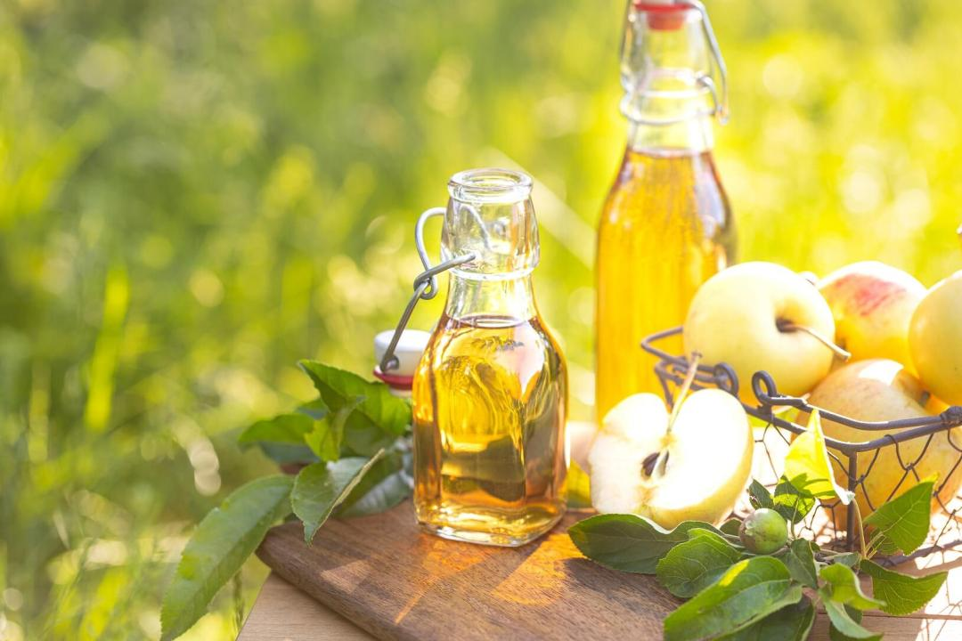 How to make Apple Juice - Two Bottles with Apple Juice with Fresh apples on wooden Plate